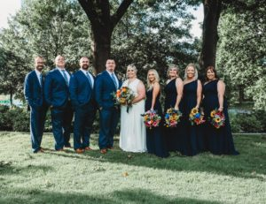 Melissa poses with her husband and entire bridal party in her sleeveless sleek wedding gown