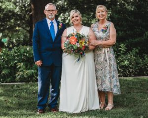 Melissa gets to pose with mom and dad in her sleeveless sleek wedding gown.